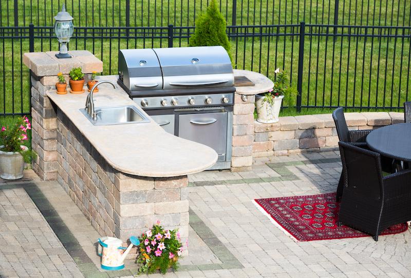 Stylish outdoor kitchen on a brick patio